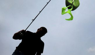 Steve McQuin of C to C Bait Company in Beaver Dam, Wis. lifts one of his company's Slop Frog lures from the waters of Beaver Dam Lake Wednesday, May 14, 2014. Amy McQuin started her career as a school teacher and later became a stay-at-home mom. She now makes bins of Slop Frog bass baits that are neatly and temporarily stored where luggage and Christmas decorations once called home. And if the plan plays out, McQuin and her husband, Steve, who runs the business side of the operation, may need to a find a bigger space for their C to C Bait Co., named after their children, Chloe, 11, and Calvin, 8. (AP Photo/Wisconsin State Journal,  John Hart)