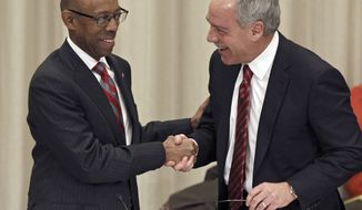 FILE - In this Jan. 30, 2014, file photo, Michael Drake, left, the incoming president at Ohio State University, shakes hands with Robert Schottenstein, chairman of the Ohio State University board, after Drake was named president during a board meeting in Columbus, Ohio. Newly released documents show Ohio State University spent more than $600,000 on the search for its new president. (AP Photo/Paul Vernon, File)