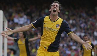 Atletico's Diego Godin from Uruguay, celebrates after scoring his side's first goal during a Spanish La Liga soccer match between FC Barcelona and Atletico Madrid at the Camp Nou stadium in Barcelona, Spain, Saturday, May 17, 2014. (AP Photo/Andres Kudacki)