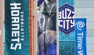 Josh Carr attaches new vertical Charlotte Hornets logo signs outside of Time Warner Cable Arena on Monday, May 19, 2014, in Charlotte, N.C. In preparation for Tuesday's official name change, the Charlotte Bobcats began branding Time Warner Cable Arena with Charlotte Hornets sings. (AP Photo/The Charlotte Observer, Jeff Siner)