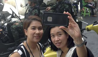 Residents stop to take a photograph of themselves at a military checkpoint in central Bangkok, Thailand, Tuesday, May 20, 2014. Thailand's army declared martial law in a surprise announcement before dawn Tuesday that it said was aimed at keeping the country stable after six months of sometimes violent political unrest. The military, however, denied a coup d'etat was underway. (AP Photo/Kiko Rosario)