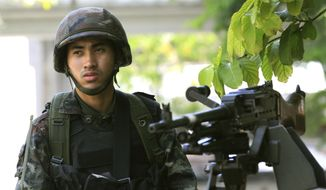 A Thai soldier stands guard outside the Thai police headquarters Tuesday, May 20, 2014, in Bangkok, Thailand. Thailand's army declared martial law before dawn Tuesday in a surprise announcement it said was aimed at keeping the country stable after six months of sometimes violent political unrest. The military, however, denied a coup d'etat was underway.  (AP Photo/Sakchai Lalit)
