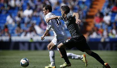 Real Madrid's Gareth Bale, left, duels for the ball with Espanyol's Javier Lopez during a Spanish La Liga soccer match at the Santiago Bernabeu stadium  in Madrid, Spain, Saturday, May 17, 2014 . (AP Photo/Daniel Ochoa de Olza)