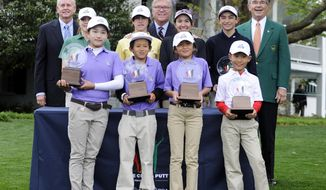 FILE - In this April 6, 2014 file photo, Lucy Li, front left, poses with winners of the Drive, Chip and Putt contest at Augusta National in Augusta, Ga. Li has become the youngest player to qualify for the U.S. Women's Open by winning the sectional qualifier at Half Moon Bay in California. The 11-year-old Li shot rounds of 74-68 on the par-72 Old Course on Monday, May 19, 2014. Others in then photo are, back row, from left, Ted Bishop, president of The PGA of America; Tom O'Toole, president of the U.S. Golf Association; and Billy Payne, chairman of Augusta National Golf Club. From left in middle row are Girls 12-13 category winner Natalie Pietromonaco, overall Boys 12-13 category winner Bryson Bianco, overall Girls 14-15 category winner Hunter Pate and overall Boys 14-15 category winner Patrick Welsh. In front from left are overall Girls 10-11 category winner Lucy Li, overall Boys 10-11 category winner Leo Cheng, overall Girls 7-9 category winner Kelly Xu and overall Boys 7-9 category winner Treed Huang. (AP Photo/The Augusta Chronicle, Rainier Ehrhardt)