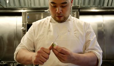 FILE - This April 9, 2008 file photo shows chef David Chang preparing vegetables for dinner at Momofuku Ko in New York. Momofuko Ko is Chang's third restaurant and the hardest to get into, thanks to a new online reservation system that doesn't play favorites and the fact that the restaurant only has 12 seats. (AP Photo/Seth Wenig, File)