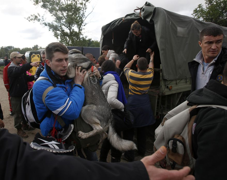 A man holds his dog during the evacuation from floods in Obrenovac, some 30 kilometers (18 miles) southwest of Belgrade Serbia, Saturday, May 17, 2014. Record flooding in the Balkans leaves at least 20 people dead in Serbia and Bosnia and is forcing tens of thousands to flee their homes. Meteorologists say the flooding is the worst since records began 120 years ago. (AP Photo/Darko Vojinovic)