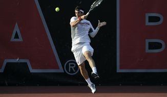 Oklahoma's Guillermo Alcorta returns a shot to Southern California's Connor Farren and Roberto Quiroz during a men's doubles match in the NCAA Division I team tennis championships, Tuesday, May 20, 2014, in Athens, Ga. (AP Photo/David Tulis)