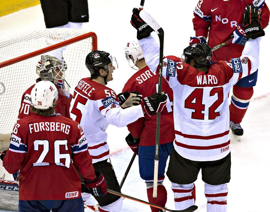 Team Canada's Joel Ward, right, is joined by teammate Mark Scheifele after scoring the winning goal against Norway's goalie Steffen Soberg during third period action on Tuesday, May 20, 2014 at the IIHF World Hockey Championship in Minsk, Belarus. (AP Photo/The Canadian Press, Jacques Boissinot)