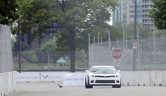 A Camaro is driven on the Chevrolet Detroit Belle Isle Grand Prix course in Detroit, Tuesday, May 20, 2014, during media hot lap rides. The Detroit Grand Prix has reached a two-year extension with Chevrolet to keep a race on Belle Isle through at least 2016. Auto racing returned to Detroit in 2012 following a four-year absence thanks in part to a three-year deal with Chevy. Without the new contract, this year's IndyCar races could have potentially been the last ones scheduled in the Motor City. (AP Photo/Carlos Osorio)