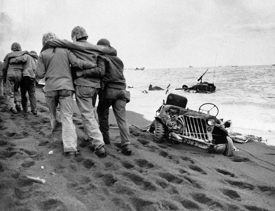 The going is hard in the volcanic sand as wounded Marines are held by fellow Marines, less seriously wounded, and Navy medical corpsmen bound for an aid station on Jan. 27, 1945, during the invasion of Iwo Jima, Japan. Around them is wrecked American equipment, on the beach and in the water. Four weeks of fighting for the little Island cost the Marines 25,851 casualties, of whom 5,931 were killed. (AP Photo)