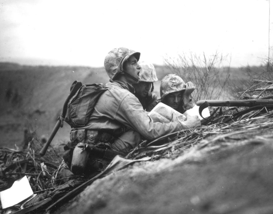 During the invasion on Iwo Jima, in February 1945, advancing U.S. troops spot a Japanese machine gun nest ahead of them. One of the men is establishing its location on the map, so they can forward the information to artillery or mortar units to wipe out these positions. (AP Photo)
