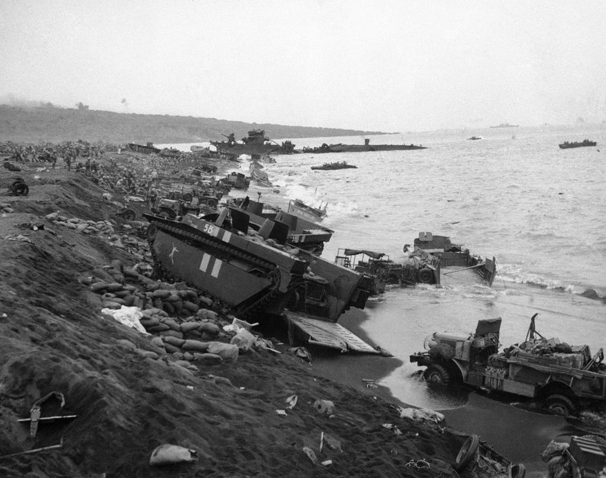 """Amtracs and trucks used by the """"Fighting Fourth"""" Marine Division as it battled its way ashore at Iwo Jima, Japan, litter the black sands of the beach of D-Day on Feb. 19, 1945. First aid stations (background) were set up among the debris of wrecked and blasted Amtracs, landing barges, jeeps and trucks. (AP Photo/U.S. Marine Corps)"""