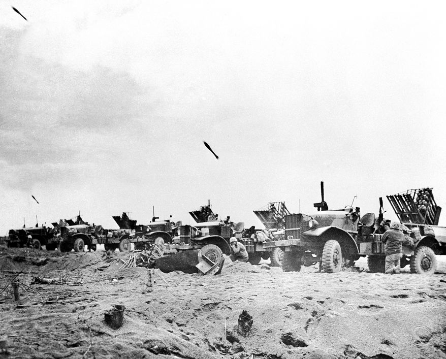 Fourth Division Marines are pinned down by enemy fire as they hit the beach at Iwo Jima on D-Day, Japan on Feb. 19, 1945. Making their fourth amphibious assault in 13 months, the veteran fighters are ready to secure the fight flank of the initial beachhead. (AP Photo/Tech. Sgt. H. Neil Gillespie/U.S. Marine Corps)