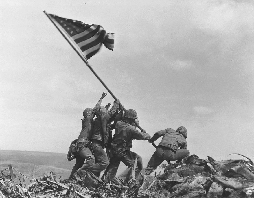 U.S. Marines of the 28th Regiment, 5th Division, raise the American flag atop Mt. Suribachi, Iwo Jima, on Feb. 23, 1945. Strategically located only 660 miles from Tokyo, the Pacific island became the site of one of the bloodiest, most famous battles of World War II against Japan.  (AP Photo/Joe Rosenthal)