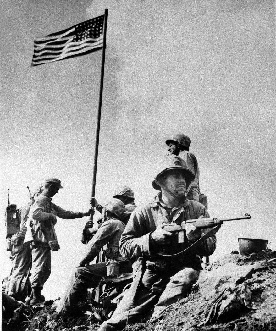 A U.S. Marine from the 5th Division of the 28th Regiment stands guard atop Mt. Suribachi at Iwo Jima in the Volcano Islands of Japan as others hoist the American flag during World War II, Feb. 23, 1945.  This was the first flag raised by the Marine Corps at Iwo Jima, a second larger one was raised later that day.  (AP Photo/Louis R. Lowery)
