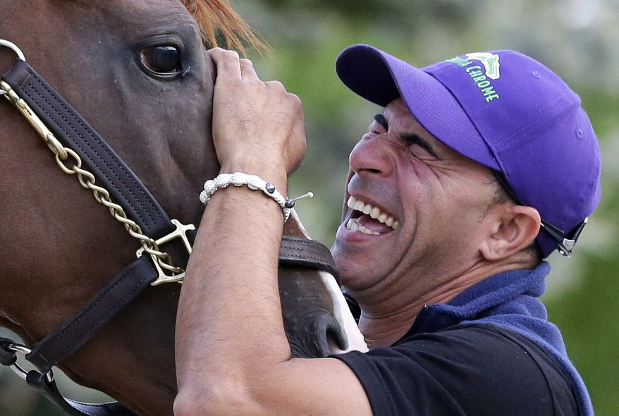 Exercise rider Willie Delgado laughs as he waits to guide Kentucky Derby and Preakness winner California Chrome onto a trailer at Pimlico Race Course in Baltimore, Tuesday, May 20, 2014.  The horse is headed to Belmont Park in Elmont, N.Y, where the Belmont Stakes horse race is scheduled to take place June 7. (AP Photo/Patrick Semansky)