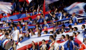 Supporters of Yokohama F. Marinos cheer during  a J-League soccer match between Marinos and Kawasaki Frontale in Kawasaki, near Tokyo, Sunday, May 18, 2014. (AP Photo/Shuji Kajiyama)