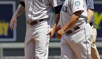 Seattle Mariners manager Lloyd McClendon, right, and a trainer help Mariners' Corey Hart, left, off the field after Hart injured his leg while stealing second base during the fourth inning of a baseball game against the Minnesota Twins in Minneapolis, Sunday, May 18, 2014. The Mariners won 6-2. (AP Photo/Ann Heisenfelt)