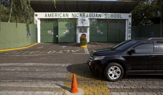 FILE - This Wednesday, May 7, 2014 file photo, shows the main entrance gate of the American Nicaraguan School, one of the international schools that hired a teacher believed to be one of the most prolific pedophiles in memory, in Managua, Nicaragua. The American Nicaraguan School said in an email to parents and staff Tuesday, May 20, 2014, that director Gloria Doll resigned, effective June. (AP Photo/Esteban Felix, File)