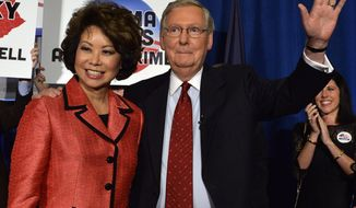 ** FILE ** Kentucky Sen. Mitch McConnell, right, and his wife Elaine Chao wave to his supporters following his victory in the Republican primary Tuesday, May 20, 2014, at the Marriott Louisville East in Louisville, Ky. (AP Photo/Timothy D. Easley)