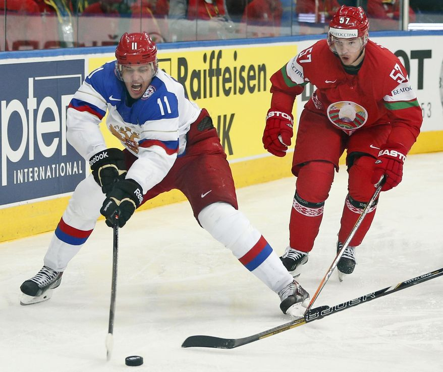 Russia forward Evgeni Malkin, left, battles for the puck with Belarus defender Ivan Usenko during the Group B preliminary round match between Russia and Belarus at the Ice Hockey World Championship in Minsk, Belarus, Tuesday, May 20, 2014. (AP Photo/Darko Bandic)