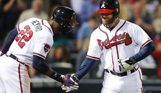 Atlanta Braves pinch hitter Ryan Doumit, right, celebrates with Jason Heyward after hitting a solo home run against Milwaukee Brewers in the eighth inning of a baseball game Monday, May 19, 2014, in Atlanta. Atlanta won 9-3. (AP Photo/John Bazemore)