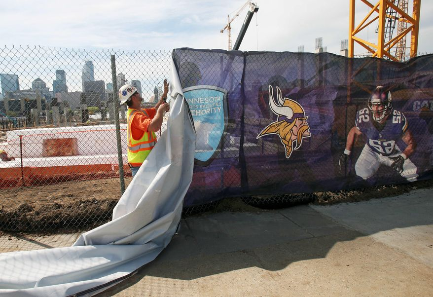 The Minneapolis skyline rises in the background as a construction worker takes down a logo wrap from a fence as work  continues on the new Minnesota Vikings NFL football stadium, Tuesday, March 20, 2014, in Minneapolis. Minneapolis will host the 2018 Super Bowl after a vote by owners Tuesday rewarded the city for its new stadium deal. (AP Photo/Jim Mone)