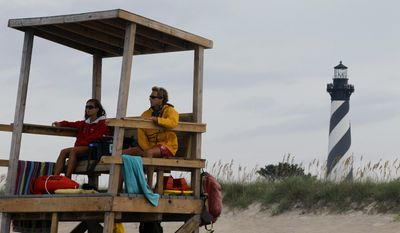 FILE - In this Aug. 24, 2011 file photo, lifeguards keep watch over the beach along the Cape Hatteras National Seashore in Buxton, N.C. A report released Tuesday, May 20, 2014 by the Union of Concerned Scientists says that the Cape Hatteras Lighthouse is one of two dozen landmarks nationwide threatened by rising sea levels. (AP Photo/Gerry Broome, file)