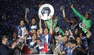 Paris Saint Germain's Thiago Motta, center, holds the trophy as he celebrates PSG's French League One title, at the Parc des Princes Stadium, in Paris, Saturday, May. 17, 2014. (AP Photo/Jacques Brinon)