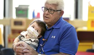 ADVANCE FOR WEEKEND MAY 24-26 - In this May 9, 2014 photo, nine-month-old Jayson Olguin-Lugo, of Arcadia, leans against Holtz Children's Hospital volunteer Juan Manfredi during a quiet moment in Miami. Olguin-Lugo had a heart transplant in April. Manfredi, 72, of Hollywood, volunteers at Holtz Children's Hospital at Jackson Memorial Hospital in Miami three times a week inspired by his granddaughter who died in 2003. (AP Photo/The Miami Herald, Marsha Halper)