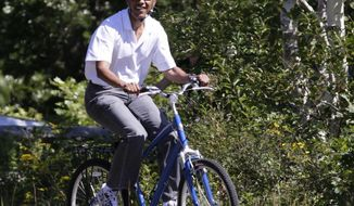 President Barack Obama rides bicycles with his family, not seen, in Manuel F. Correllus State Forest in West Tisbury, Mass., while the first family vacations on Martha's Vineyard, Friday, Aug. 27, 2010. (AP Photo/Carolyn Kaster)
