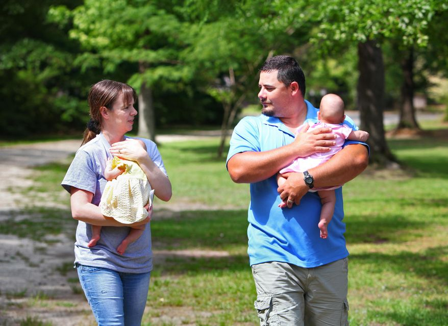 ADVANCE FOR USE SATURDAY, MAY 24, AND THERAFTER - In this May 9, 2014 photo, Matt, right, and Amanda Segura hold their twin daughters Jordyn, right, and Jayden, outside their Round O, S.C. home. Jayden was born at 22 weeks, and Jordyn five weeks later. Doctors believe Jayden is one of the smallest babies ever born in South Carolina that has survived. (AP Photo/The Post And Courier, Wade Spees)  LOCAL TV OUT; LOCAL PRINT OUT; THE STATE OUT