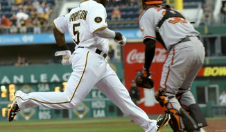 Pittsburgh Pirates' Josh Harrison (5) dashes home to score as Baltimore Orioles catcher Caleb Joseph waits for the relay throw in the first inning of the baseball game on Wednesday, May 21, 2014, in Pittsburgh . (AP Photo/Keith Srakocic)