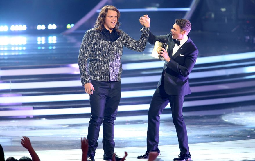 Ryan Seacrest, right, announces Caleb Johnson the winner at the American Idol XIII finale at the Nokia Theatre at L.A. Live on Wednesday, May 21, 2014, in Los Angeles. (Photo by Paul A. Hebert/Invision/AP)