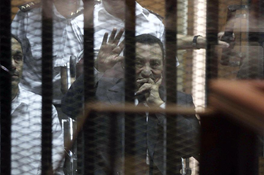 Ousted Egyptian President Hosni Mubarak, sitting in a defendants cage, waves during a court hearing as his son Gamal, left, in Cairo, Egypt, Wednesday, May 21, 2014. An Egyptian court has convicted Mubarak of embezzlement and sentenced him to three years in prison. Mubarak's two sons, one-time heir apparent Gamal and wealthy businessman Alaa, were also convicted Wednesday of graft and sentenced to four years in prison each in the same case. (AP Photo/ Hassan Mohammed)