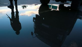 An armed Thai soldier is reflected in a puddle as he guards a road near a pro-government demonstration site on the outskirts of Bangkok. Thailand's army chief Gen. Prayuth Chan-Ocha assumed the role of mediator Wednesday by summoning the country's key political rivals for face-to-face talks one day after imposing martial law. (Associated Press photographs)