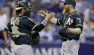 Oakland Athletics relief pitcher Sean Doolittle, right, shakes hands with catcher Derek Norris after the Athletics defeated the Tampa Bay Rays 3-2 in a baseball game Wednesday, May 21, 2014, in St. Petersburg, Fla. (AP Photo/Chris O'Meara)