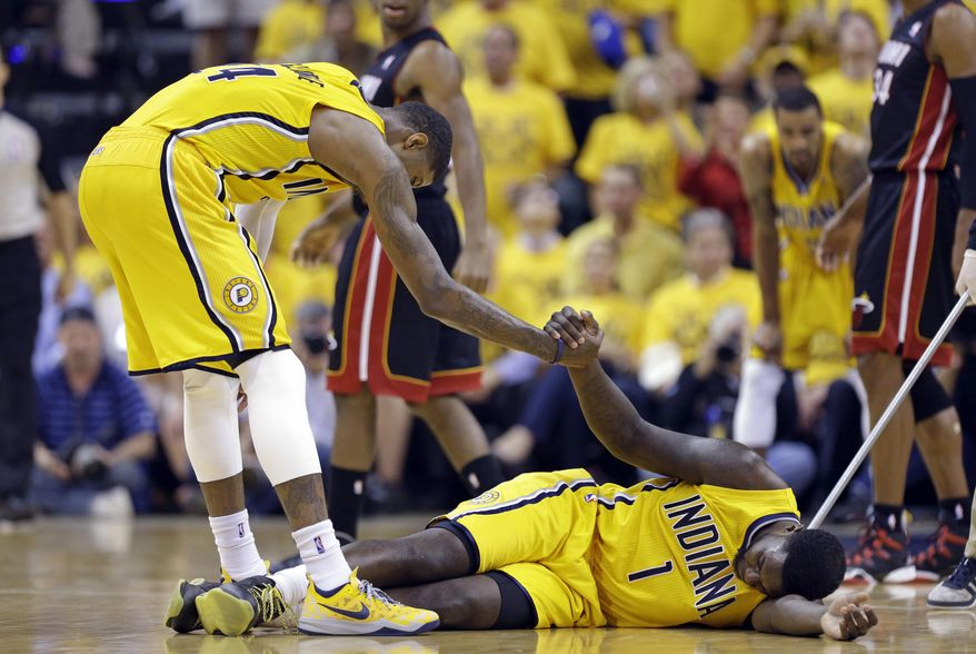 Indiana Pacers forward Paul George helps guard Lance Stephenson off the floor after Stephenson committed a foul against the Miami Heat during the second half of Game 2 of the NBA basketball Eastern Conference finals in Indianapolis, Tuesday, May 20, 2014. (AP Photo/Michael Conroy)