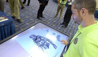 In this May 20, 2014 photo, Michael Fieldson , the civilian project manager for the Tactical Assault Light Operator Suit at McDill Air Force Base, looks at sketches of the body armor exoskeleton during the Special Operations Forces Industry Conference in Tampa, Fla. Elite US special operations forces may be a few short years away from donning a similar suit. (AP Photo/Tamara Lush)