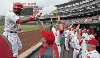 Washington Nationals' Denard Span, left, celebrates his solo home run with his teammates during the first inning of a baseball game against the Cincinnati Reds at Nationals Park Wednesday, May 21, 2014, in Washington. (AP Photo/Alex Brandon)