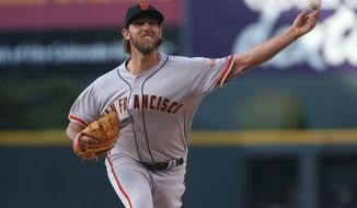 San Francisco Giants starting pitcher Madison Bumgarner works against the Colorado Rockies in the first inning of a baseball game in Denver on Tuesday, May 20, 2014. (AP Photo/David Zalubowski)