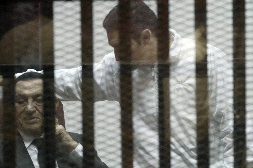 Ousted Egyptian President Hosni Mubarak, sits in a defendants cage, with his son Alaa, right, during a court hearing in Cairo, Egypt, Wednesday, May 21, 2014. An Egyptian court has convicted Mubarak of embezzlement and sentenced him to three years in prison. Mubarak's two sons, one-time heir apparent Gamal and wealthy businessman Alaa, were also convicted Wednesday of graft and sentenced to four years in prison each in the same case. (AP Photo/ Hassan Mohammed)