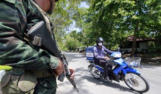 A Thai soldier looks at a motorcyclist riding past while providing security near the pro-government demonstration site on the outskirts of Bangkok, Thailand Wednesday, May 21, 2014. Thailand began its second day under martial law Wednesday with little visible military presence on the streets of Bangkok as residents tried to make sense of the dramatic turn of events after six months of anti-government protests and political turmoil. (AP Photo/Wason Wanichakorn)