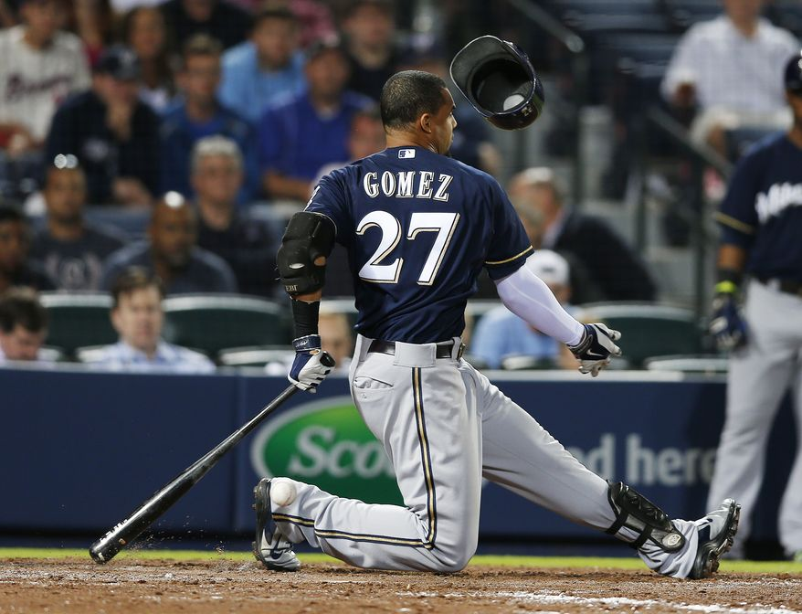 Milwaukee Brewers center fielder Carlos Gomez (27) loses his helmet as he swings and misses in the seventh inning of a baseball game against Atlanta Braves Monday, May 19, 2014 in Atlanta. (AP Photo/John Bazemore)