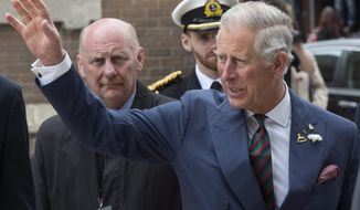 Prince Charles waves to the crowd while crossing a street Wednesday, May 21, 2014 in Winnipeg. The Royal couple are on a four-day tour of Canada. (AP Photo/The Canadian Press, Paul Chiasson)