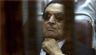 ** FILE ** In this Saturday, April 26, 2014, file photo, ousted Egyptian President Hosni Mubarak attends a hearing in his retrial over charges of failing to stop killings of protesters during the 2011 uprising that led to his downfall, in the  Police Academy-turned-court in the outskirts of Cairo, Egypt. (AP Photo/Tarek el Gabbas, File)