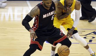 Miami Heat forward LeBron James, left, gets the ball knocked loose by Indiana Pacers forward Paul George during the second half of Game 2 of the NBA basketball Eastern Conference finals in Indianapolis, Tuesday, May 20, 2014. The Heat won 87-83. (AP Photo/AJ Mast)