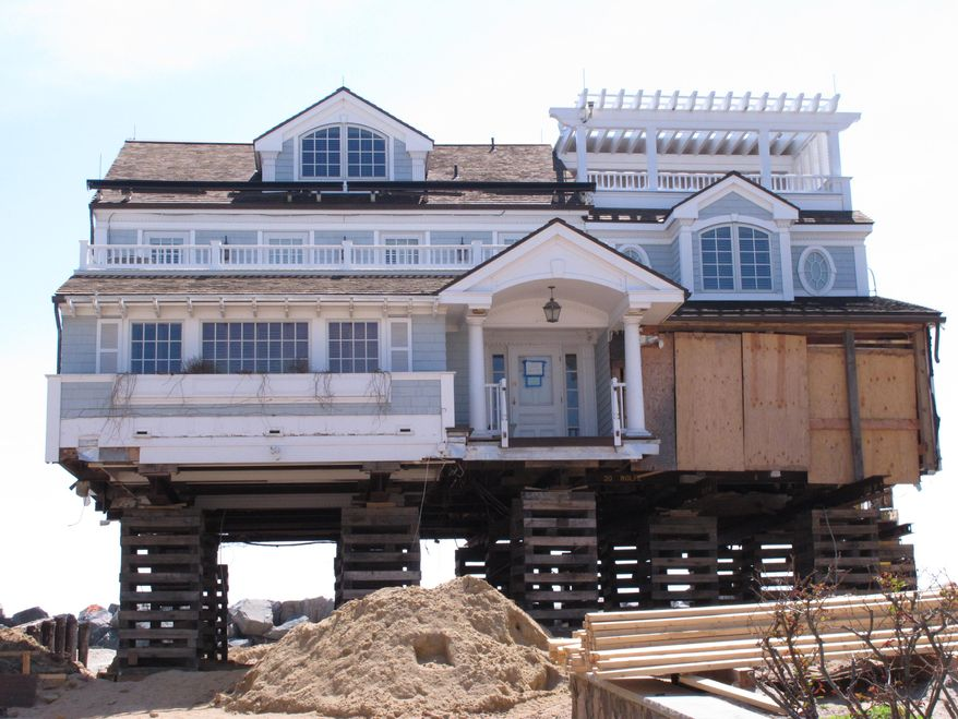 In this May 12, 2014 photo, a house on the Mantoloking N.J. beachfront is being elevated to protect against future storms like Superstorm Sandy. As the second summer after the Oct. 29, 2012 storm arrives, some at the Jersey shore are getting their lives back together, while for others, getting back to normal is still a long way off. (AP Photo/Wayne Parry)