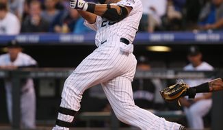 Colorado Rockies' Wilin Rosario follows the flight of his RBI-double against the San Francisco Giants in the fourth inning of a baseball game in Denver on Tuesday, May 20, 2014. (AP Photo/David Zalubowski)