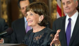 Super Bowl bid co-chair Marilyn Carlson Nelson shows her enthusiasm during a news conference at the state Capitol, Wednesday, May 21, 2014, in St. Paul. Minn., where Gov. Mark Dayton, right, hosted the presentation leaders who helped bring the NFL 2018 Super Bowl football game to Minneapolis. (AP Photo/Jim Mone)